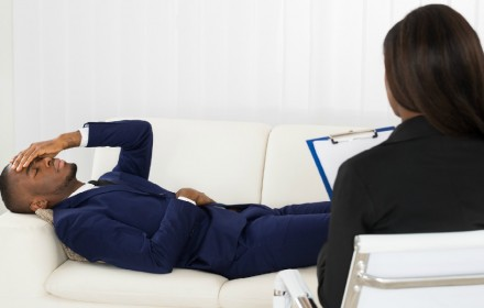 African American Man Laying On Couch In Front Of Psychiatrist With Clipboard