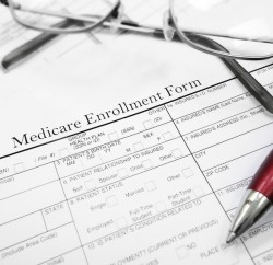 Medicare Enrollment Form document with glasses and pen