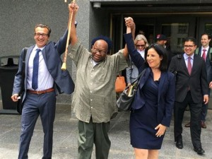 Albert Swinton raises his arms in triumph after murder charges are dismissed against him. (Innocence Project photo)