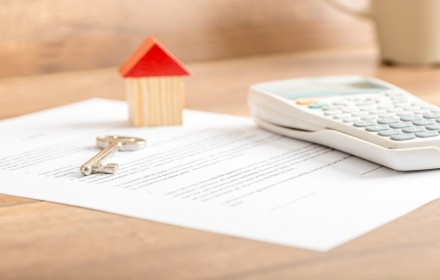 Silver house key lying on a contract for house sale
