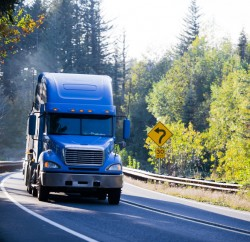 Blue semi truck and flat bed trailer on sunny green and gold autumn trees